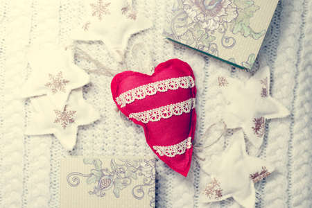 Image of handmade red heart on knitted background surrounded with decorative stars and gifts photo