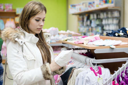 choosing selecting: Portrait of young beautiful woman selecting or choosing for buying clothes on interior store background Stock Photo