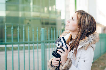 Portrait of beautiful young lady holding photo camera on city glass building background photo