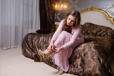 Beautiful young lady holding shoe on luxurious bedroom background photo
