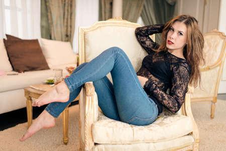 culetto di donna: Immagine di una bella giovane donna in sedia relax sul lusso sfondo interni Archivio Fotografico