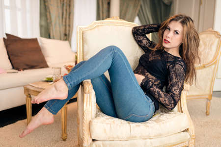 Picture of beautiful young woman relaxing in chair on luxury interior background
