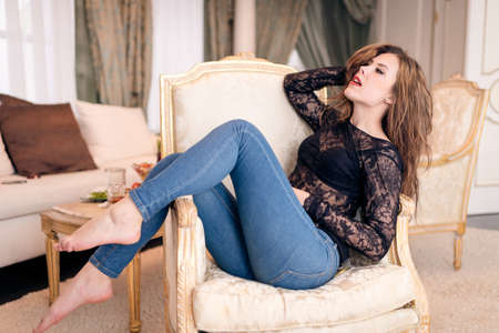 red jeans: Portrait of beautiful young lady relaxing in chair on luxury interior background Stock Photo
