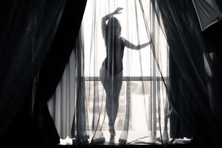 Retrato en blanco y negro de sexy hermosa joven relajante sobre fondo de ventana ligera