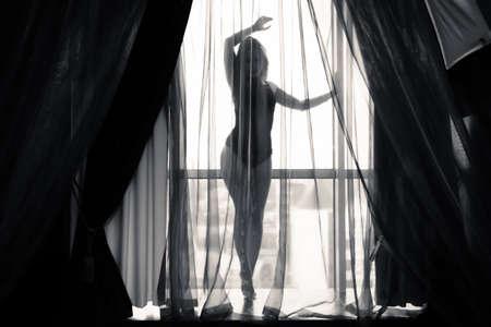 Zwart en wit portret van sexy mooie jonge dame ontspannen over lichte achtergrond venster