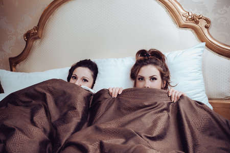 sexy couple in bed: Portrait of sexy beautiful young ladies in bed and looking at camera