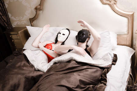 Portrait of sexy beautiful young dolls in carnival masks having fun relaxing in bed photo