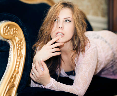 Closeup portrait of beautiful young woman relaxing lying on sofa or couch photo