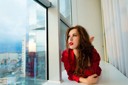 Portrait of beautiful young woman having fun relaxing looking out the window photo