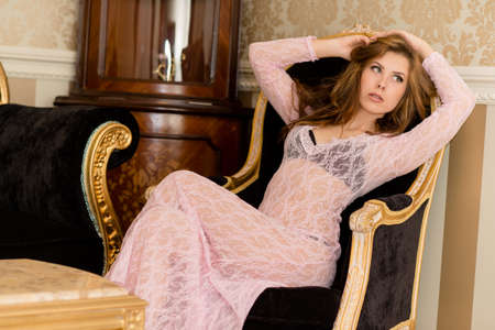 Picture of beautiful young sexy woman relaxing on chair and looking forward photo