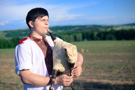 foreign land: Picture of young man playing pipes on green summer outdoors copy space background Stock Photo