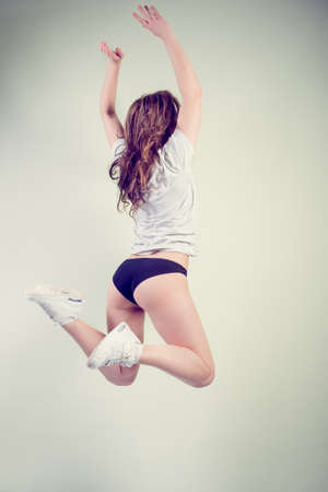Picture of sexy beautiful girl with perfectly fit body jumping high on light copy space background