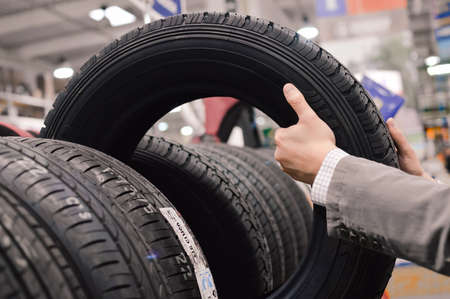 Picture closeup on hands choosing a tire or tyre