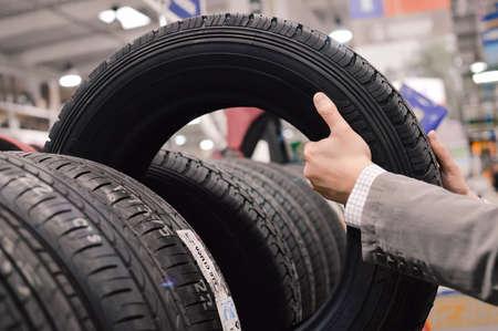 huellas de llantas: Foto de primer plano en las manos la elección de un neumático o de los neumáticos Foto de archivo