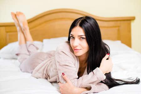 Portrait von sexy junge hübsche Dame, die Spaß entspannen liegend im weißen Bett glückliches Lächeln über hellem Hintergrund Kopie Raum