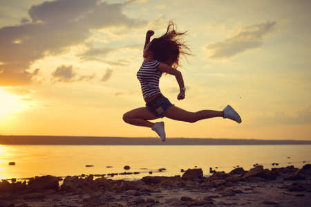 sexi: Sexi young jumping up high  in mid air on beach at sunrise