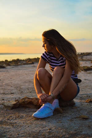 sexi: Sexi young woman sitting on beach by the sea at sunset