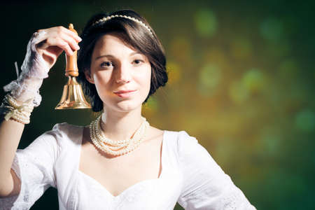 perl: Beutiful young brunette woman wearing perl beads holding a ring bell over olive background copyspace
