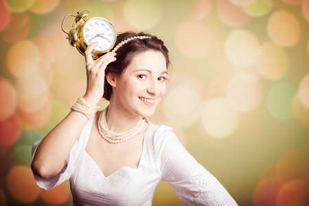 perl: Young pretty smiling girl wearing perl beads showing an alarm clock on bokeh background copyspace