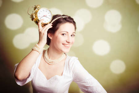perl: Studio portrait of pretty lady wearing perl beads showing an alarm clock on olive background copyspace