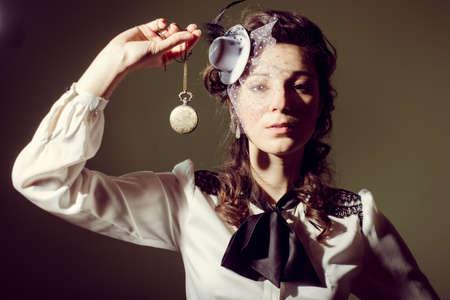 Portret van een meisje in een elegante ouderwetse kleding en stijlvolle hoed bedrijf een horloge aan een ketting