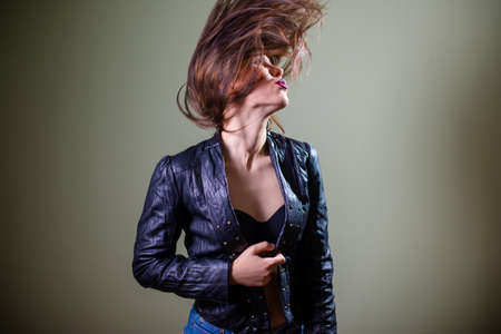 sexi: Studio shot of sensual sexi brunette female  with long hair in blue leather jacket looking away