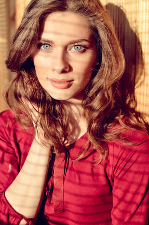 blue eyes: Portrait close up of blue eyes pretty girl with shadow from window blinds looking at camera 스톡 사진