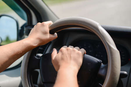 beeping: Mans hands holding a wheel of a car and beeping a horn Stock Photo