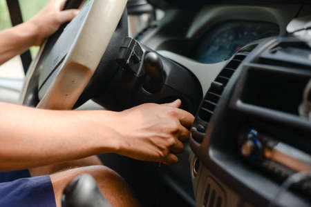 Driver turning on the ignition on the dashboard of a car