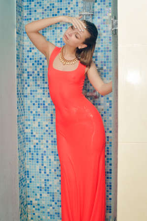 dress form: Elegant slim brunette female with long straight hair wearing  form-fitting gorgeous evening red dress taking a shower in  in shower cubicle