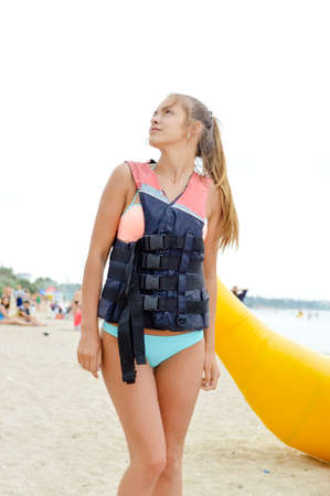 life jacket: Young beautiful slim blond female with pony tail  in life jacket walking along sandy beach ready for water adventure
