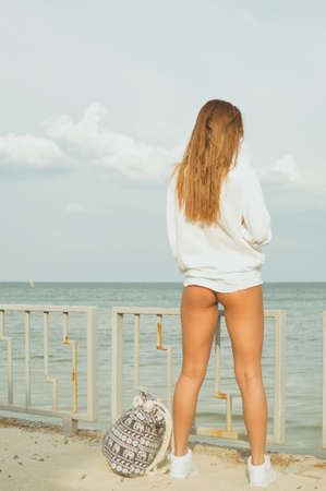 Beautiful young lady with long dark blond hair enjoying the sun on beach standing with her back to camera looking at sea