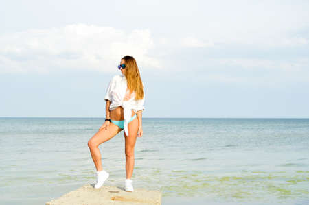 sexi: Portrait of relaxed sexi dark blond female wearing sunglasses, white shirt, swimwear and trainers on sea outdoors