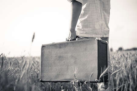 Black and white picture of mans hand holding retro suitcase outdoors over rural background