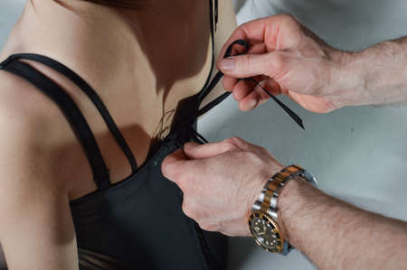 fetishes: Close up picture of mans hands with watch on wrist tie female corset in a bow