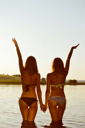 hot babe: Image of 2 sexy best girlfriends in bikini having fun together holding hands up to sky on summer sunset outdoors background copy space
