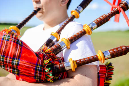 bagpipe: Closeup picture of young man playing traditional Scotland bagpipe on green summer outdoors copy space background