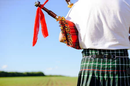bagpipe: Closeup picture of male playing bagpipe on green summer outdoors background