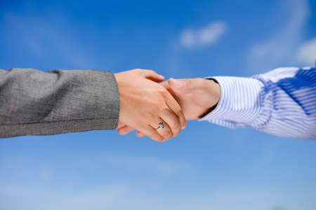 Business people handshaking on blue sky sunny outdoors background, close-up picture