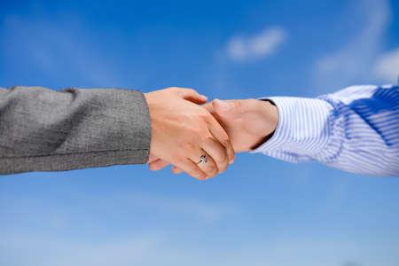Mensen uit het bedrijfsleven handshaking op de blauwe hemel zonnige buiten achtergrond, close-up foto Stockfoto