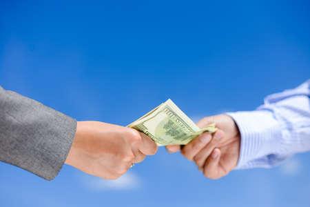 corporate greed: Picture of hands giving and receiving dollar bills. Side view in horizontal format over a blue sky sunny outdoors background.