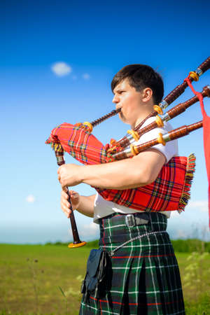 Portrait of man enjoying playing pipes in Scottish traditional kilt on green outdoors copy space summer field background Stock Photo
