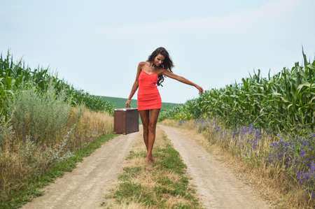 sexi: Portrait of sexi tanned girl in red short dress carrying retro suicase walking barefoot along earth road in field on summer day outdoors background Stock Photo