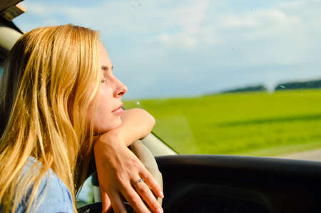 leaning on elbows: Half face closeup picture of young pretty lady waiting in car leaning elbows on wheel on summer day outdoors background with eyes closed