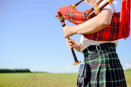 Closeup Bild der Mann im schottischen traditionellen Kilt Dudelsack spielen auf der grünen Sommer Natur Hintergrund