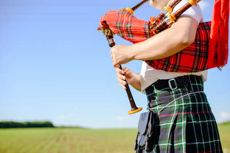 Closeup picture of male in Scottish traditional kilt playing bagpipe on green summer outdoors background
