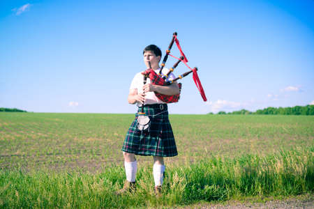 Picture of man enjoying playing pipes in Scottish traditional kilt on green outdoors summer field background copy space
