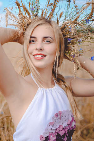 arms behind head: Closeup portrait of perfect smiling young blond lady with wheat spikelets behind her head holding arms up over rural background looking at camera