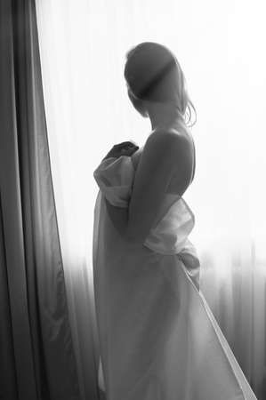 Black and white portrait of young beautiful lady hiding under white sheet standing on light window copy space background