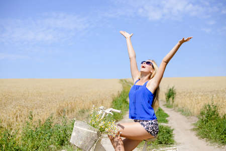 Young happy girl in blue belly shirt and shorts sitting on bicycle lifting her arms with joy riding along earth road in field of wheat, on sunny day outdoors background Standard-Bild